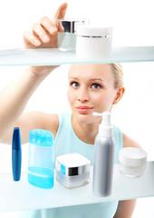 Kobieta, klientka stoi przy półce sklepowej i wybiera kosmetyki
