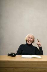 Ältere Frau sitzt am Tisch mit Buch,lachen
