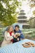 Deutschland,Bayern,München,Englischer Garten,Paar im regnerischen Biergarten hält Dach und Bierkrüge,Chinesischen Turm im Hintergrund,Portrait