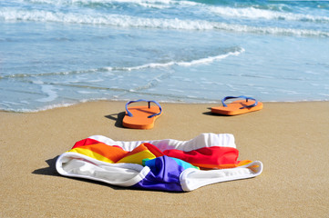 rainbow swimsuit and flip-flops in the sand of a beach