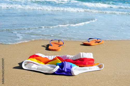 rainbow swimsuit and flip-flops in the sand of a beach - 65203147