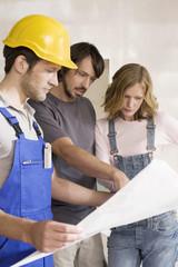 Junges Paar und Bauarbeiter Blick in die Konstruktionsplan
