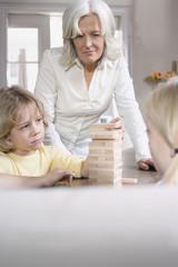 Großmutter und Enkelkinder (8-9) spielen zusammen