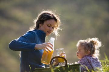 Mutter sitzt mit Tochter in Wiese,Mutter gießt Saft