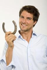 Junger Mann mit Hufeisen,Symbol für Glück