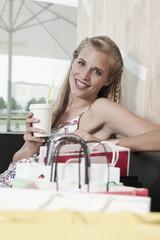 Deutschland,Köln,junge Frau im Café mit Getränken,Lächeln,Portrait
