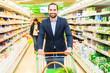 Mann mit Einkaufswagen im Supermarkt
