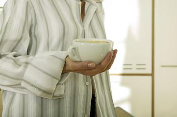 Frau hält Tasse Kaffee,Mitte Abschnitt