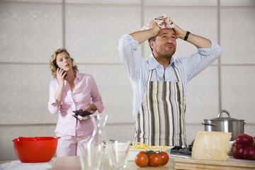 Man Kochen,Frau im Hintergrund