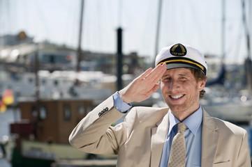 Deutschland,Hamburg,Mann salutieren mit Boot im Hintergrund,close up