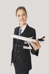 Junge Luft Stewardess mit Modellflugzeug vor weißem Hintergrund,lächelnd,Porträt