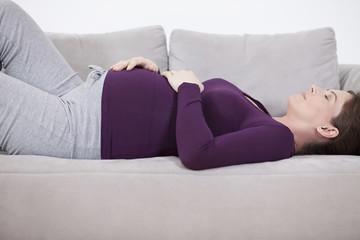Schwangere Frau liegt auf der Couch , die Augen geschlossen