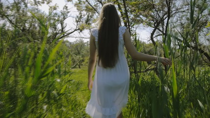Girl in white dress walking through the grass
