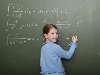Mädchen stand vor der Tafel,die Lösung von Rechenaufgabe