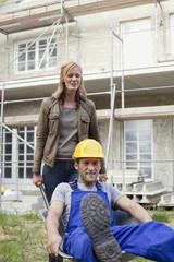 Frauen-und Bauarbeiter auf der Baustelle,Bauarbeiter sitzen in der Schubkarre