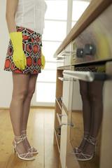 Junge Frau mit Gummihandschuhen in der Küche steht,niedrige Abschnitt
