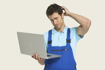 Mann im Gesamt hält Laptop und Kratzen Kopf,Portrait