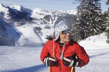 Junge Frau im Schnee hält Skistöcke
