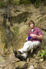 Junger Mann sitzt mit Wasserfall,Wegschauen