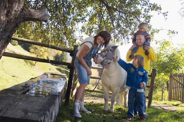 Familie mit Pony durch Brunnen