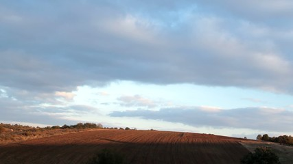 Sunset time lapse and moving clouds over the farm fields