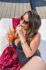 woman in bikini drinking a cocktail