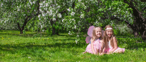 Little adorable girls with butterfly wings in the blossoming
