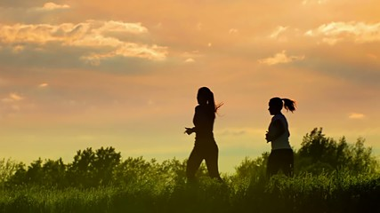 Two woman running at sunset