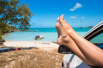 Female feet from the window of a car on background tropical