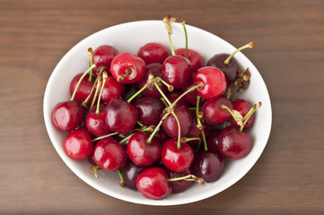 Cherries in a white dish on a wooden table