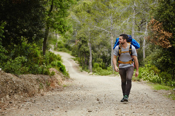 Young hiker with rucksack walking up on the trail