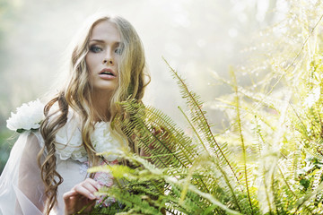 Beautiful blond woman next to the fern