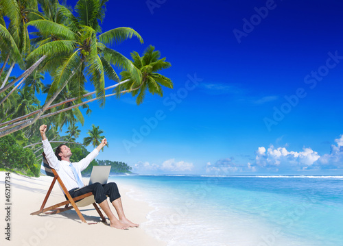 canvas print picture Businessman Relaxing on an Idyllic Palm Fringed Beach