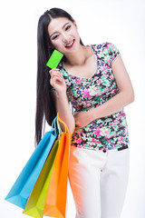young woman with shopping bags and credit card on a white backgr