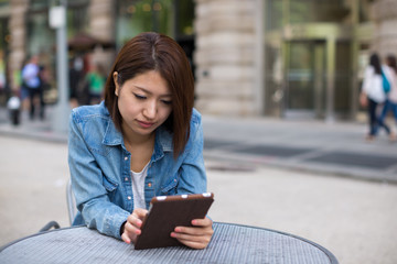 Young Asian woman in a city using tablet pc computer