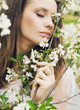 Attractive woman smelling wild flowers