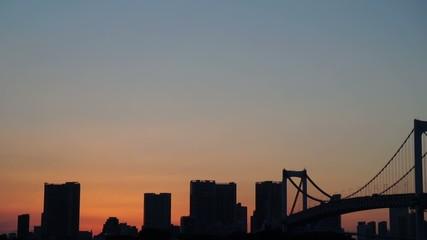 Sun setting behind Tokyo's skyscraper silhouette