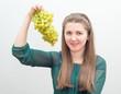 Молодая жизнерадостная девушка с виноградом