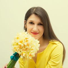 Красивая жизнерадостная темноволосая женщина с букетом цветов