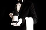 Waiter in tuxedo holding a bottle of red wine - 65222165