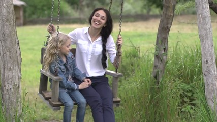 Adult woman and a little girl on a swing
