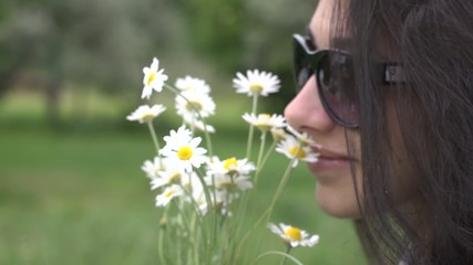 Beautiful young brunette woman smelling daisy flowers