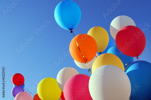 multicolored balloons in the city festival - 65223935