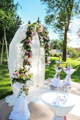 Decorated archway for wedding ceremony with colorful flowers and