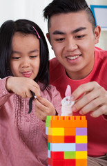 Girl with her brother playing toy blocks