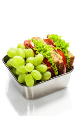 Lunch box with sandwich and grapes