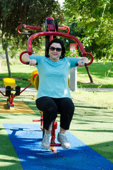 Woman training on a Lat Pull fitness machine outdoor