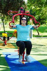 Mature woman exercising on a Lat Pull fitness station