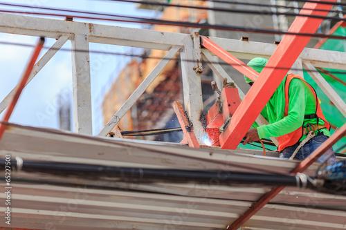 people work welding steel bars on construction site. - 65227508