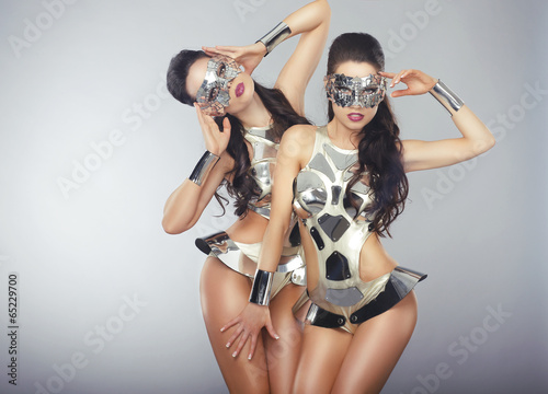 Vogue. People in Sparkling Cosmic Cyber Costumes Gesturing